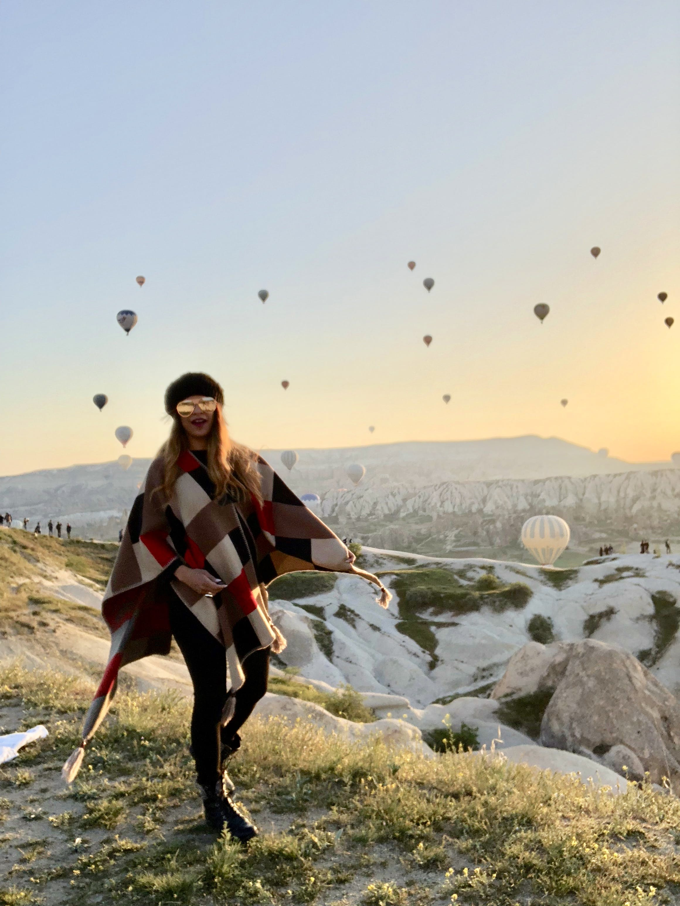 Woman Standing on Hill With Flying Hot-Air Balloons at the Back