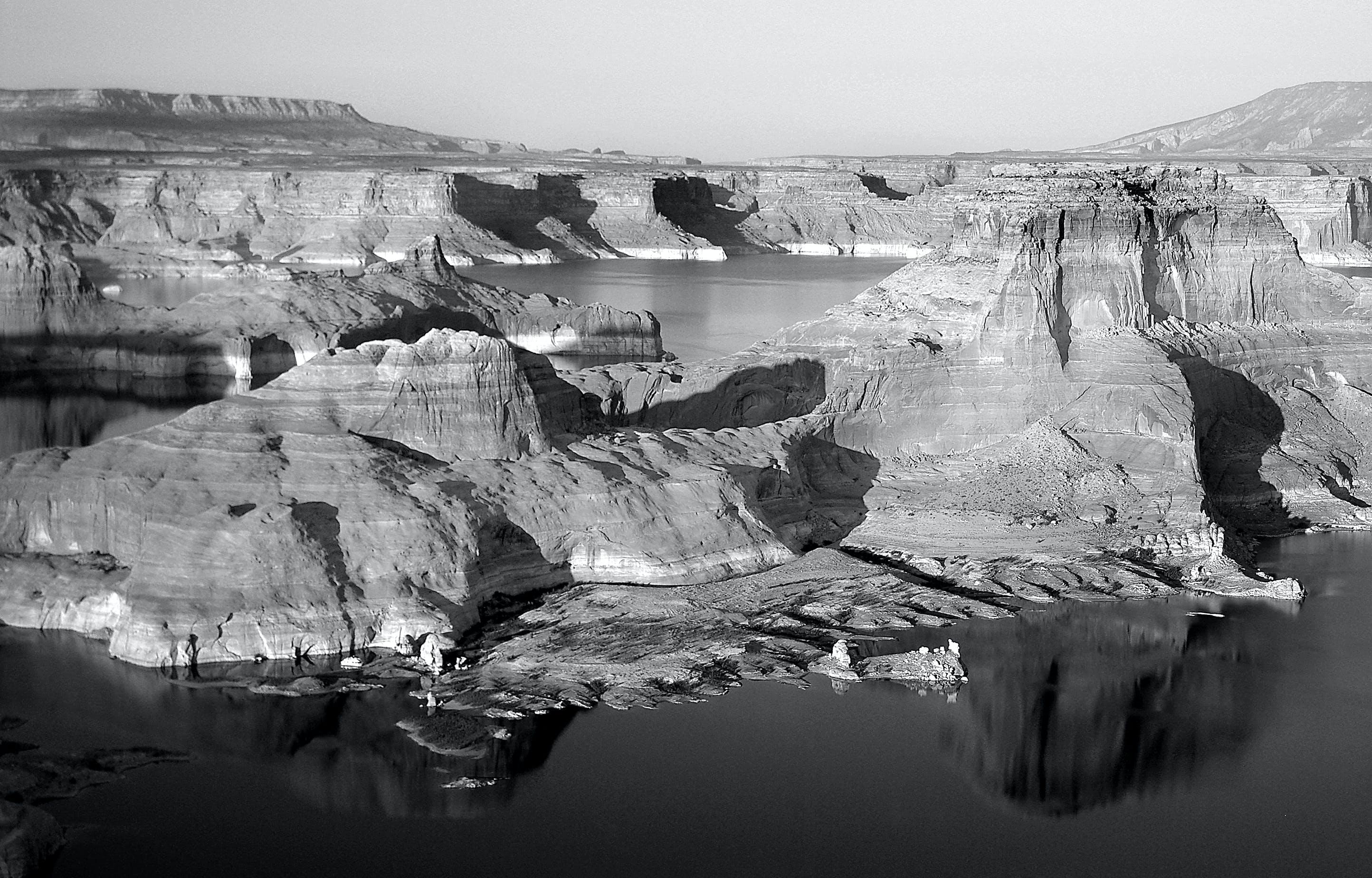 Gray Scale Photo of Mountain Beside Body of Water in Bird's Eye View