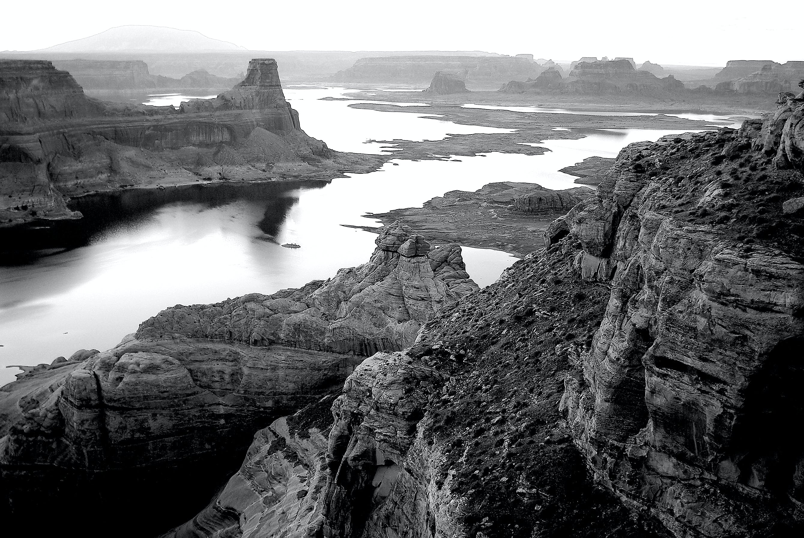 Grayscale Photography of High Rise Rock Near Body of Water