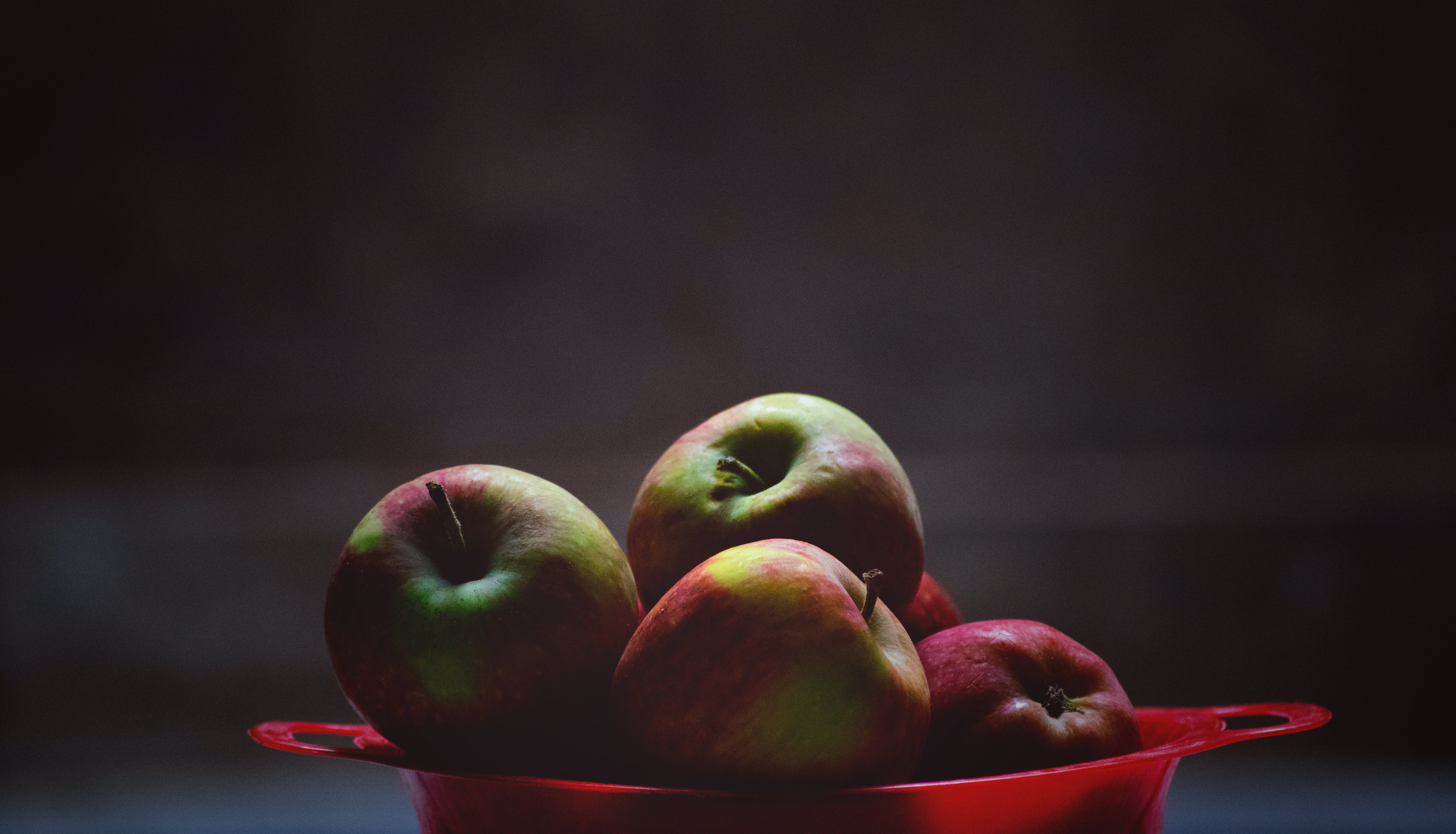 Green and Red Apple Fruits in Red Plastic Bowl