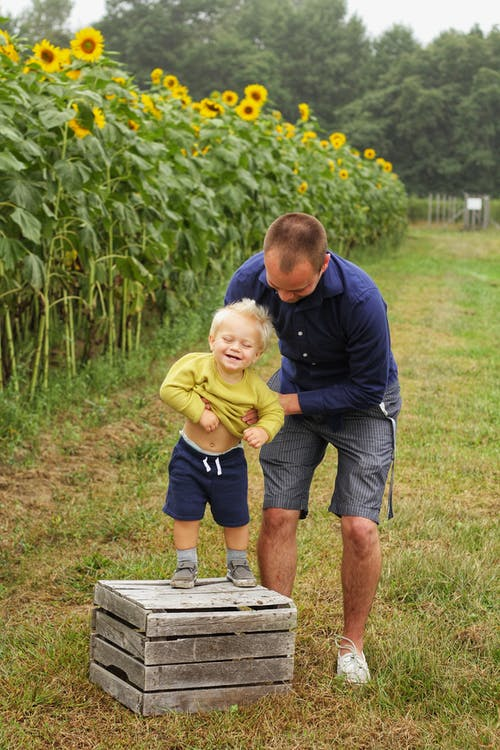 Man Holding Smiling Child Standing on Brown Wooden Crate Near Sunflowers