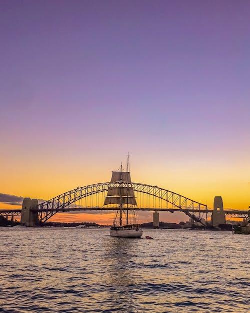 Sail Boat in Front of Bridge Under Orange Sunset