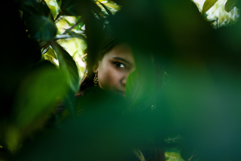 Woman Hiding Beside Tree