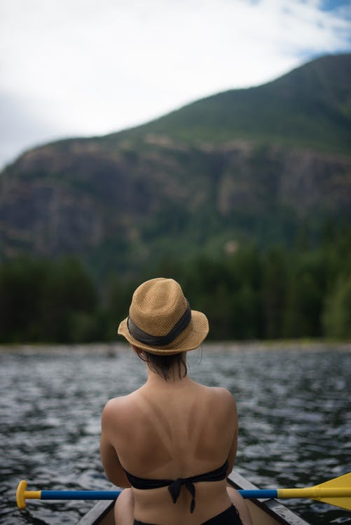 Close-up Photography of Woman Wearing Cap Riding Boat