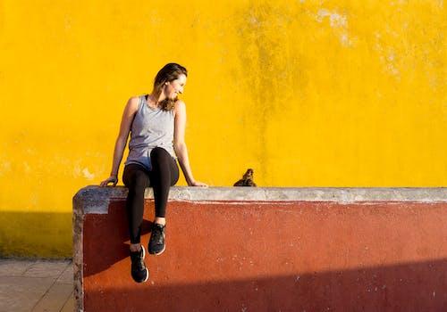 Smiling Woman Sitting on Orange Barrier