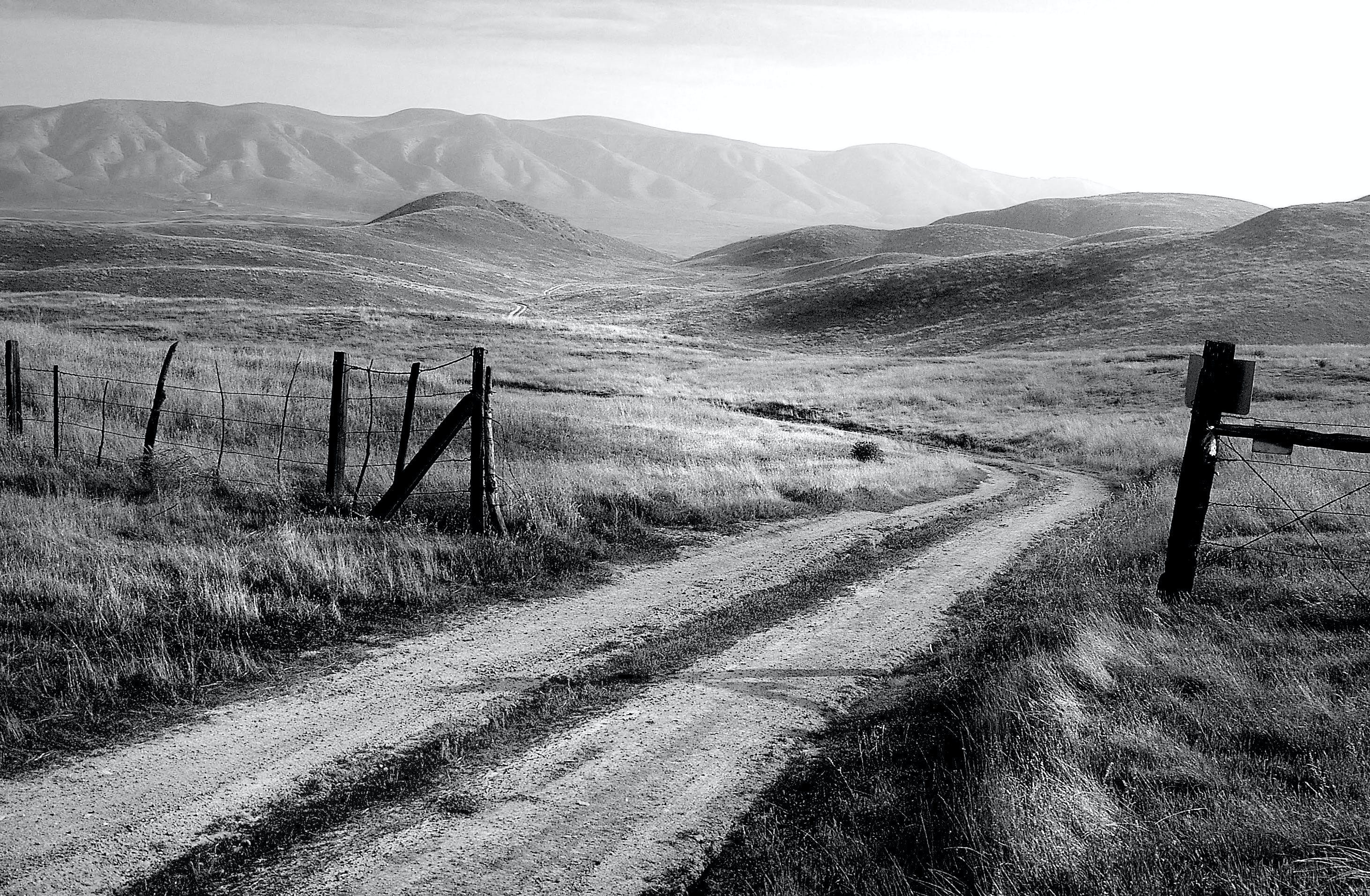 Grayscale Photo of Road and Mountain at Daytime