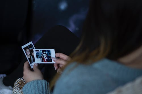 Woman Holding Two Photos