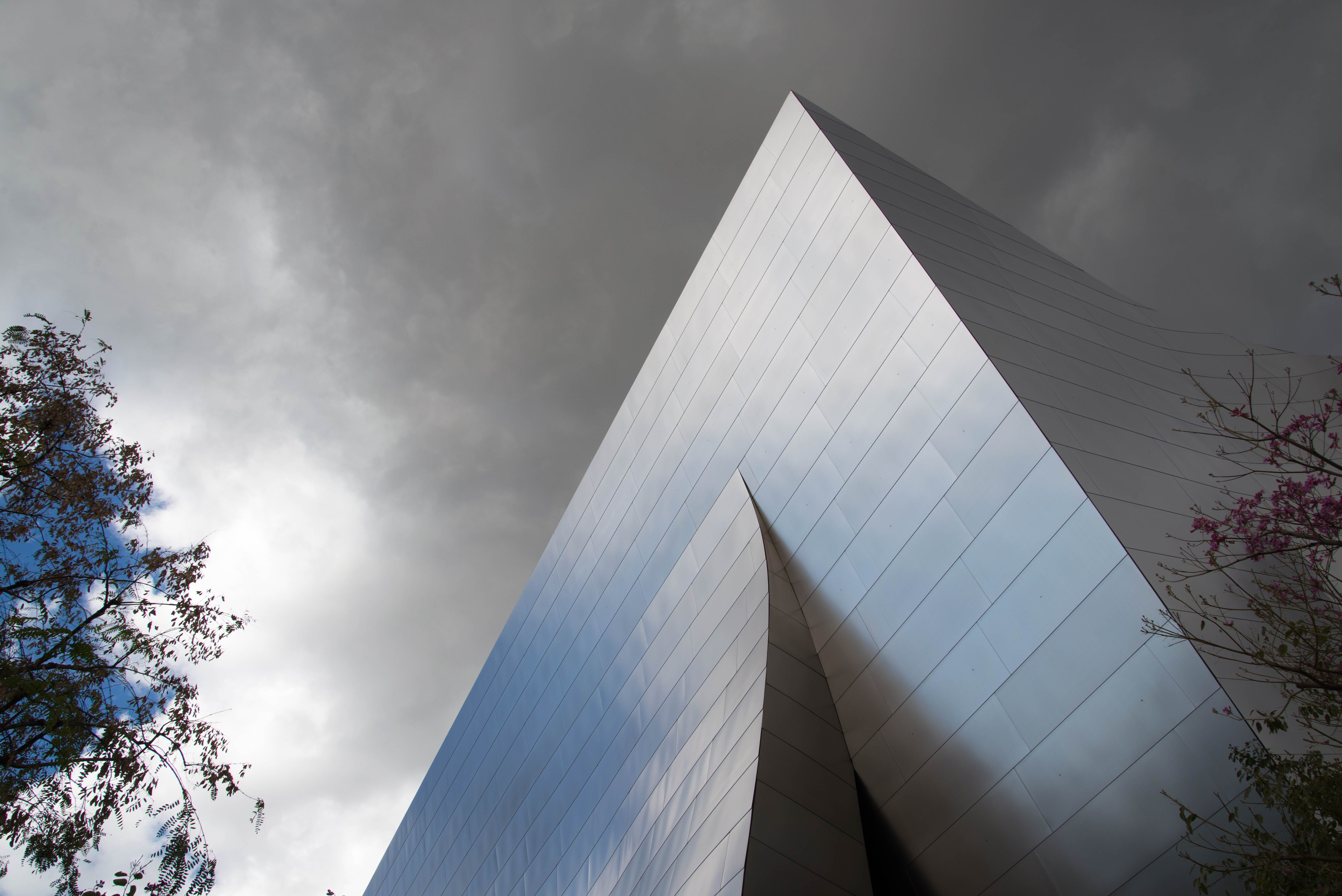Low-angle Photography of Gray Concrete Building Under Cloudy Sky