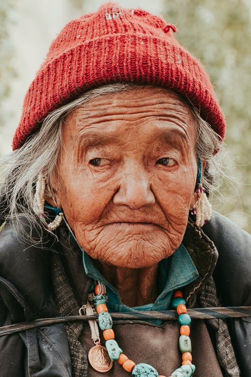 Close-Up Photo of an Old Woman Wearing Red Knit Cap
