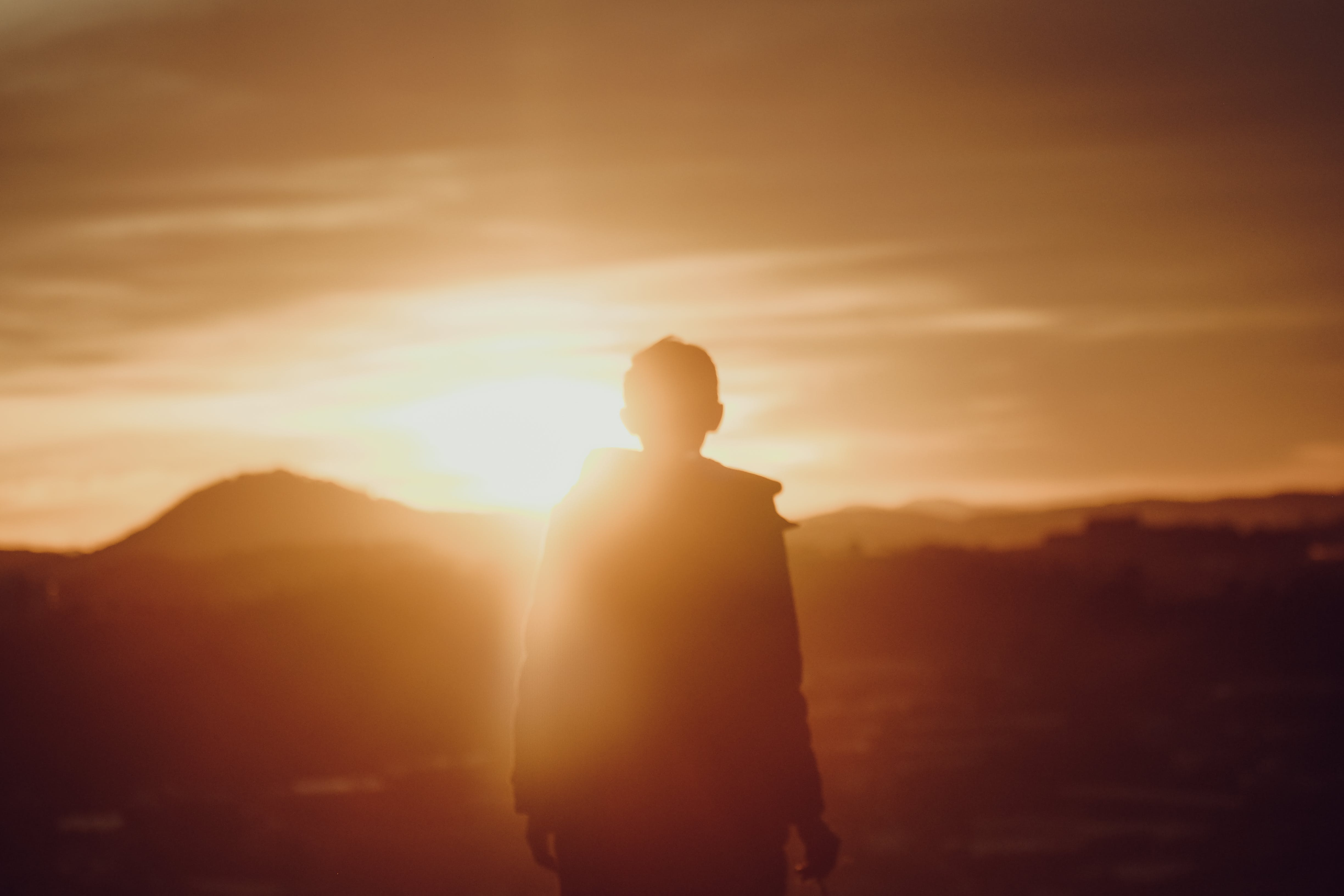 Silhouette of Person Standing Near Mountain during Sunset