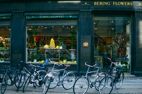 Several Assorted-color Bikes Parked in Front of Bering Flowers Facade