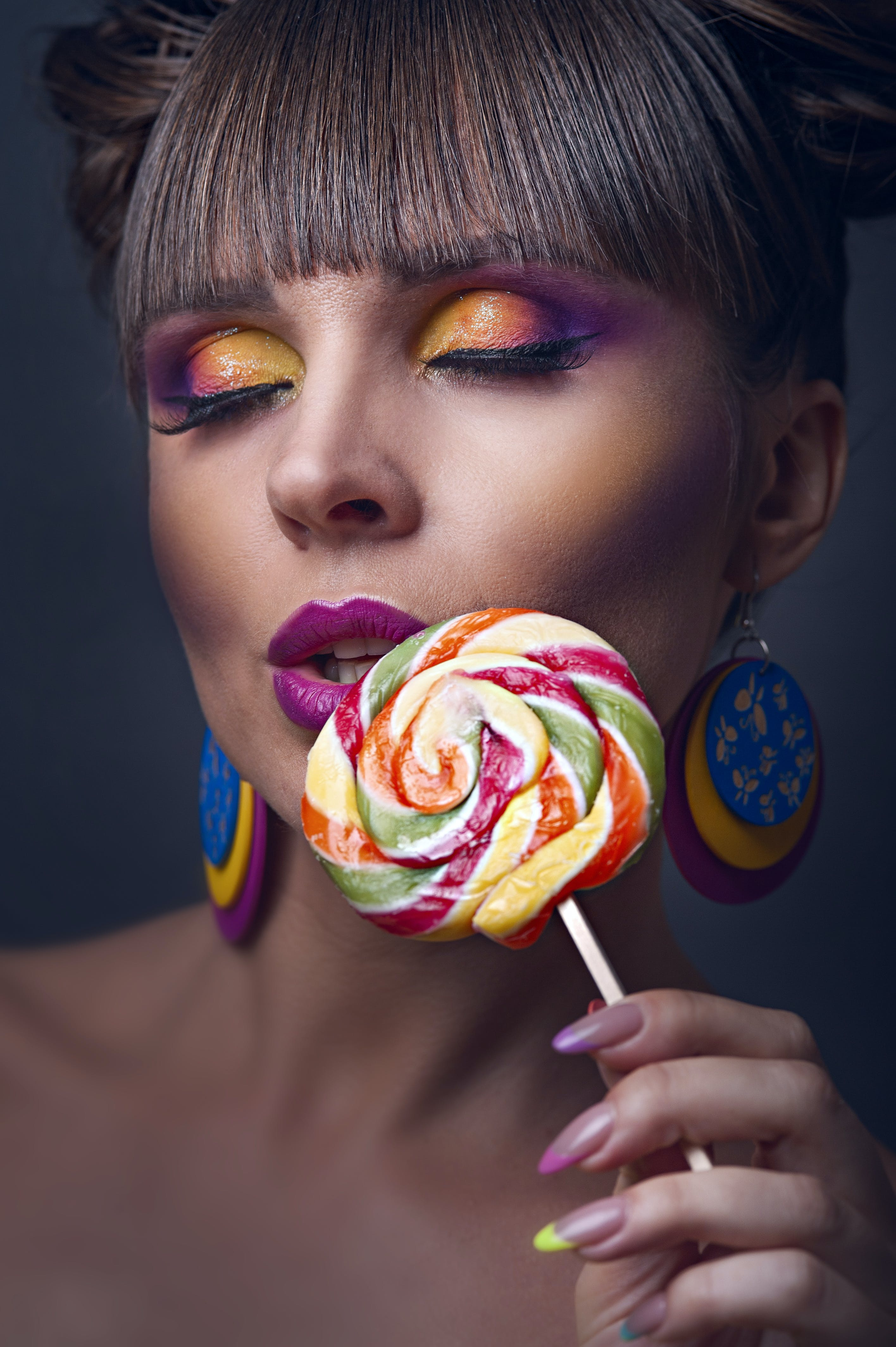 Close-UP Photo of Woman Holding Lollipop