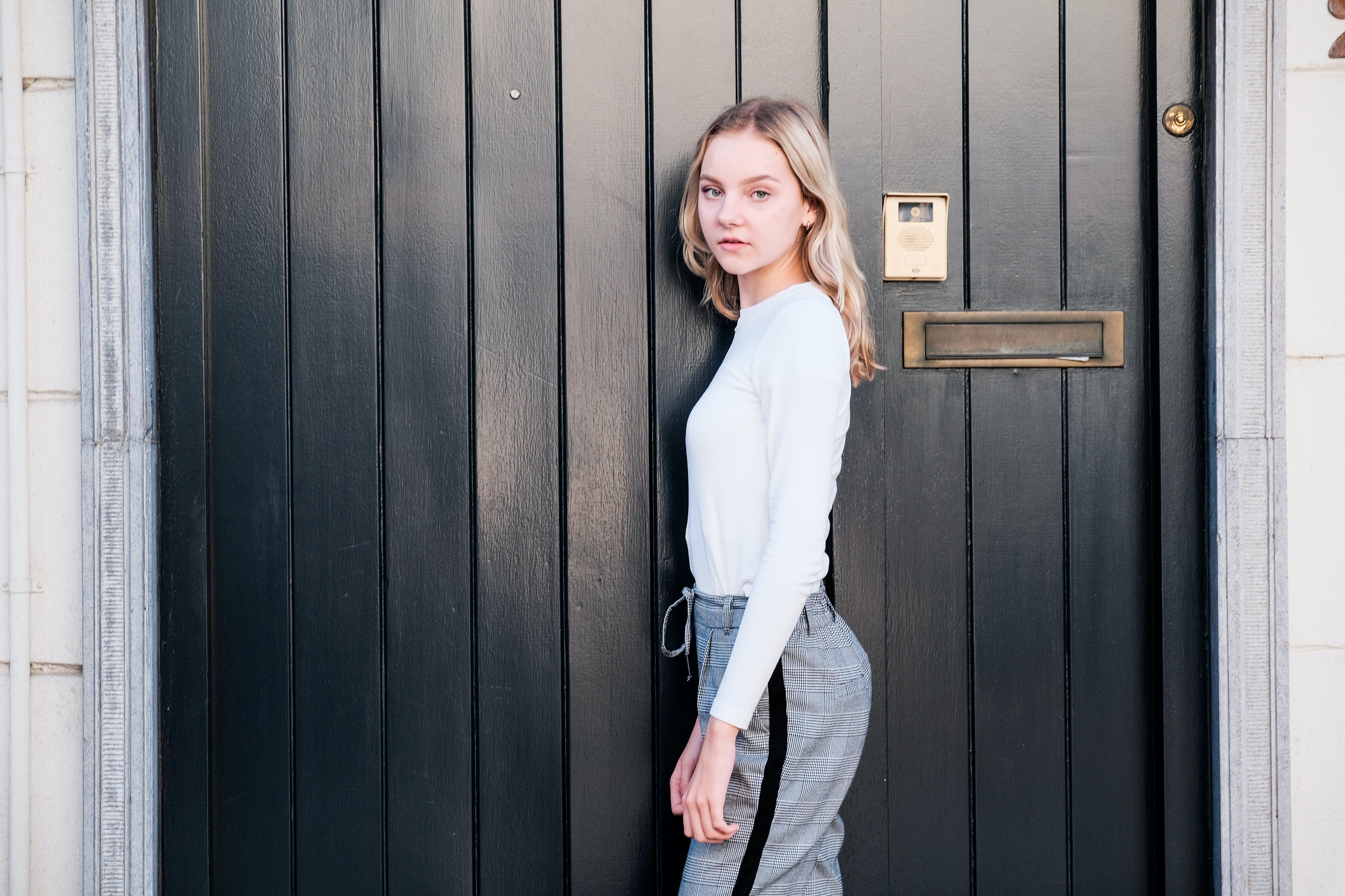 Woman Standing Beside Black Wooden Door