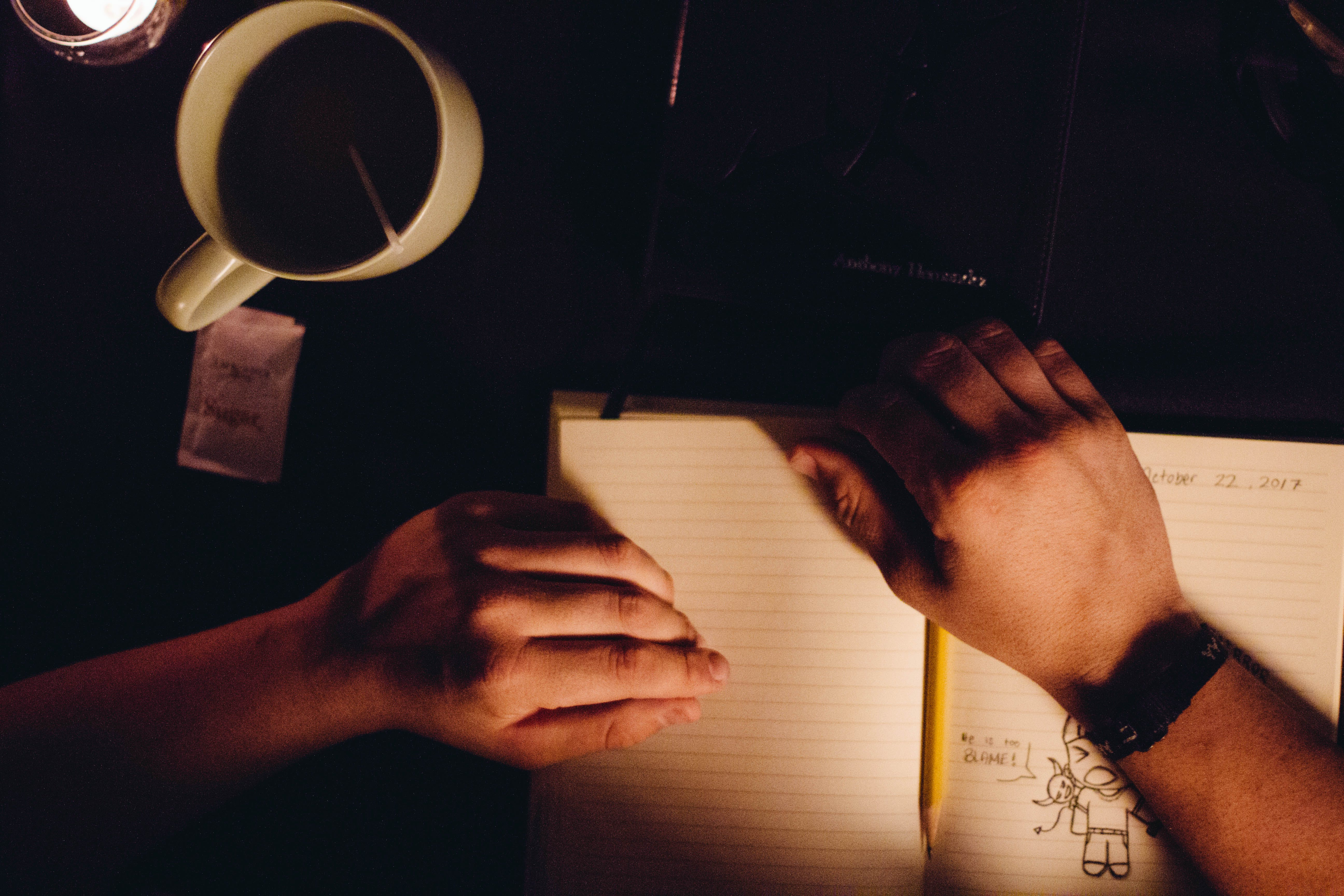 Person Holding Notebook Beside Ceramic Cup