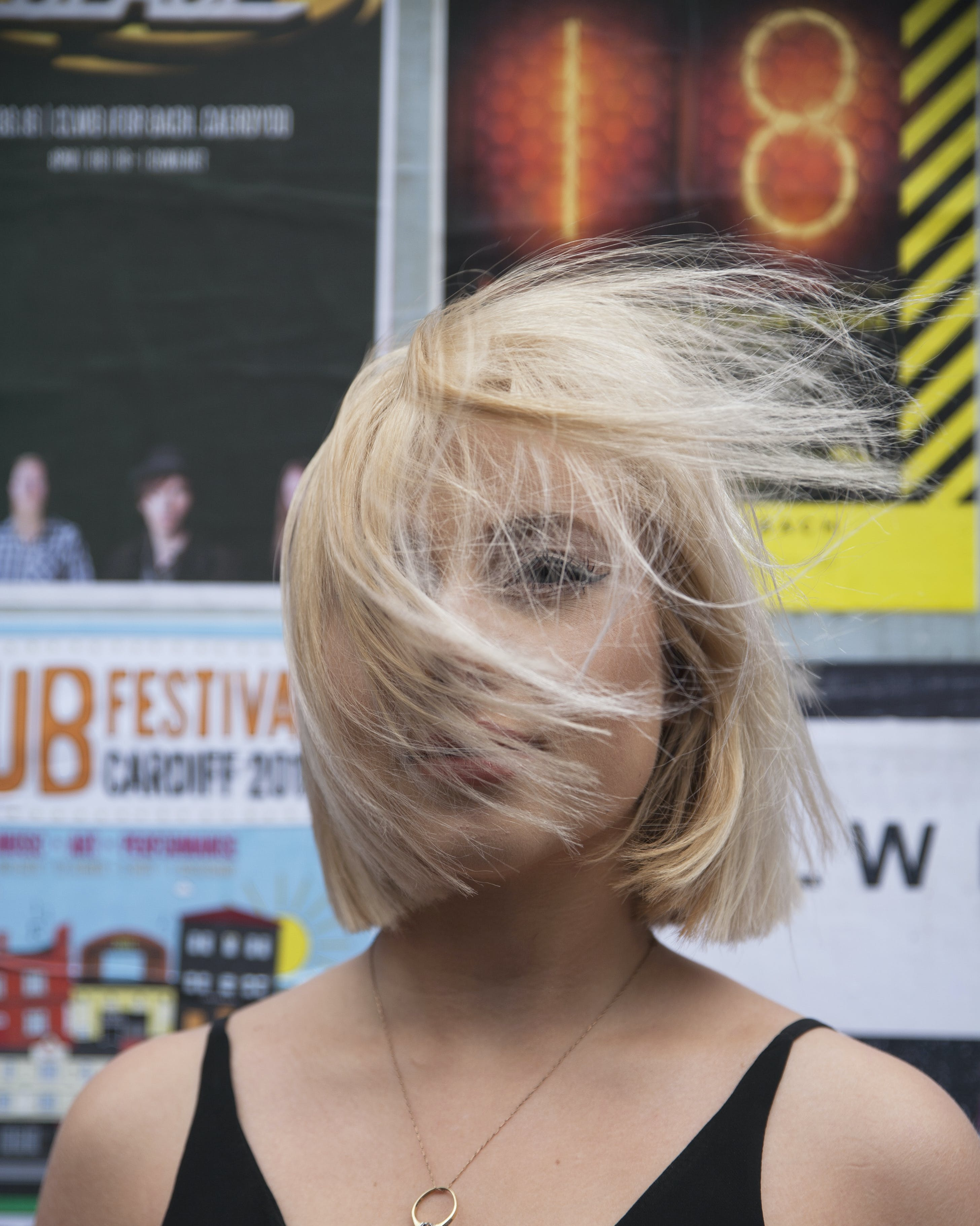 Woman With Flipping Hair Standing Near Poster