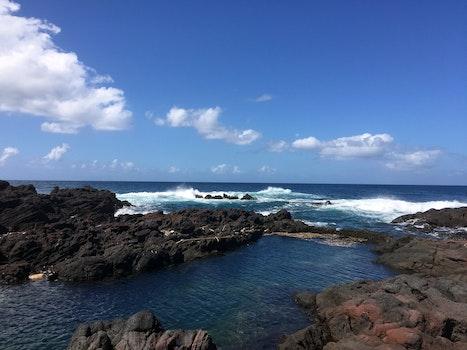 Brown Rocks Beside Ocean With Bubble Wave Under Blue Sky