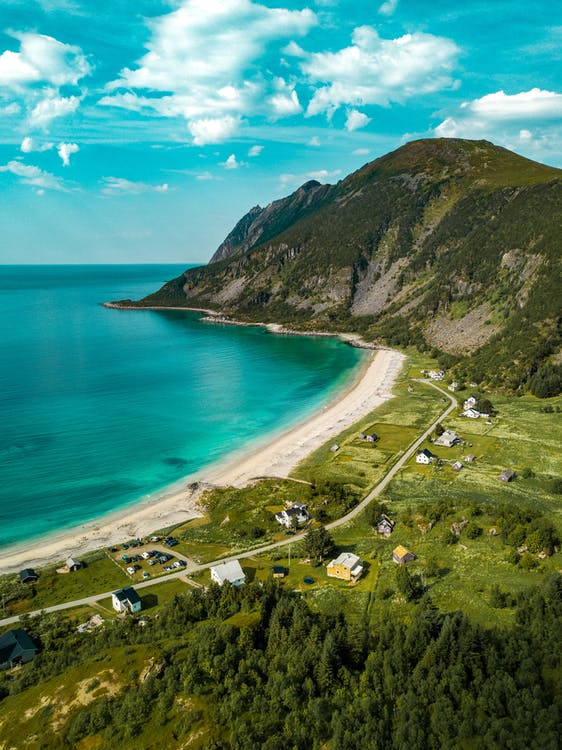 Aerial View of Shore Beside Green Mountains