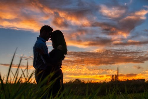 Photo of Couple Hugging During Dawn