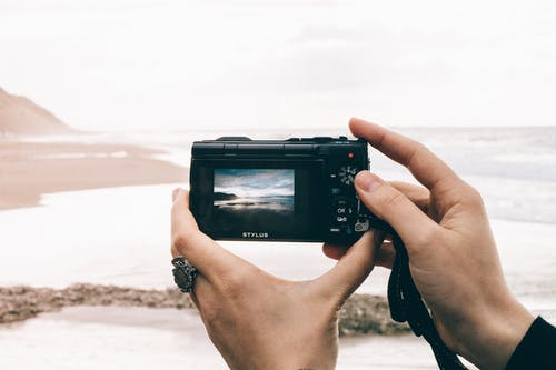 Person Taking Picture of Sea Using Point-and-shoot Camera