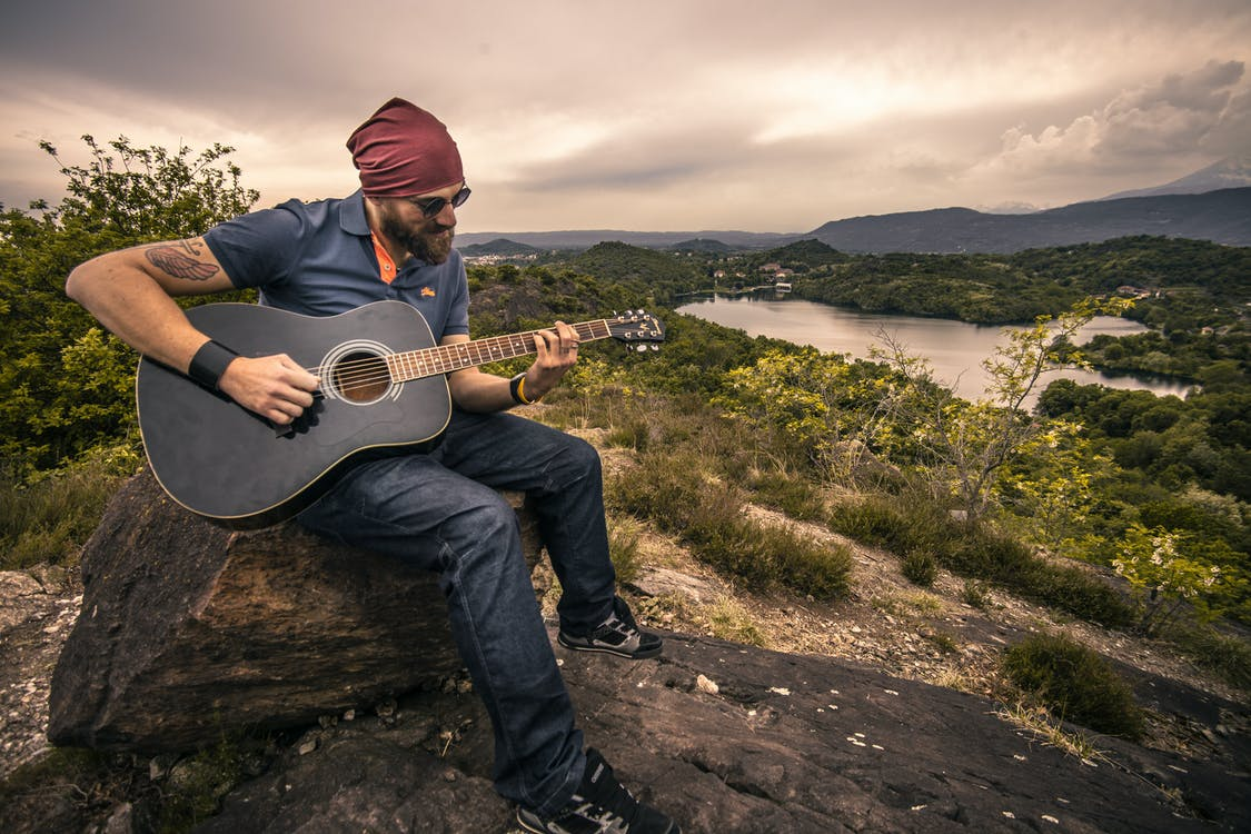 Man Playing Guitar Sitting on Brown Rock