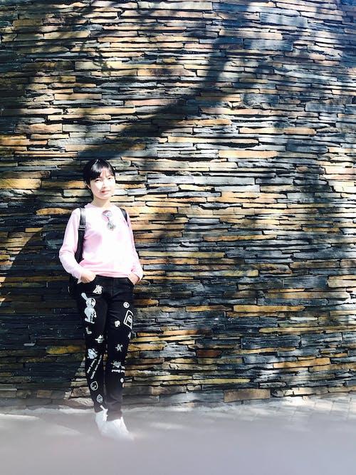 Kostenloses Stock Foto zu backsteinmauer, junge frau, sonnenbrille, sonniger tag