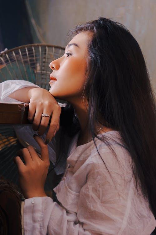 Woman In White Long-sleeved Shirt Beside Fan