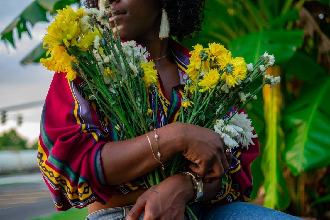 Photo of Woman Holding White and Yellow Chrysanthemum Flowers