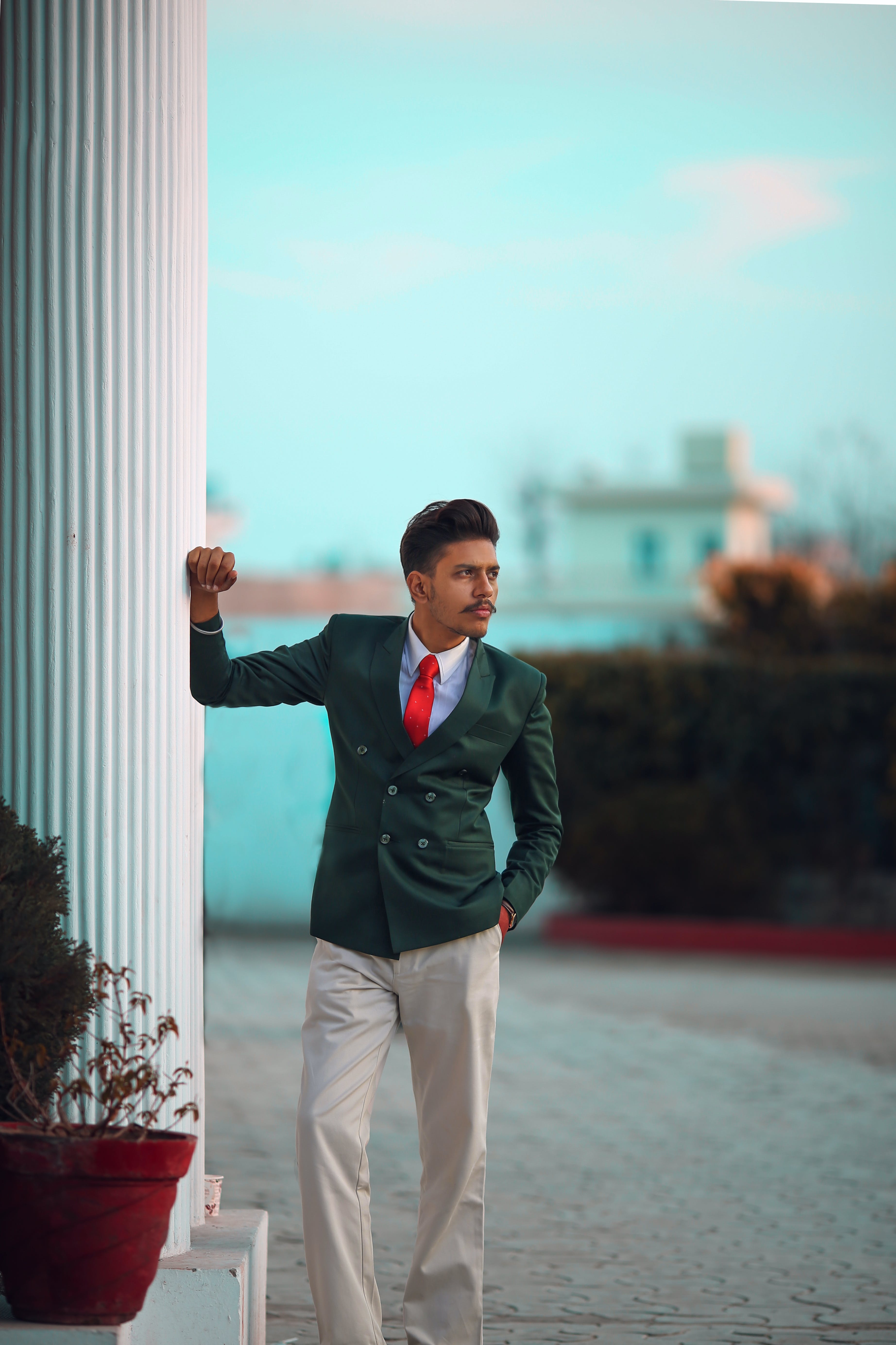 Man in Green Suit Jacket Leaning Right Hand on Column