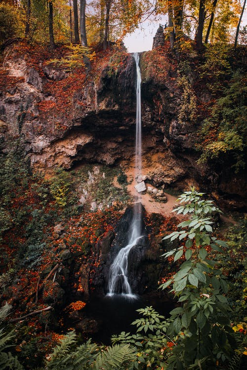 Waterfall on Cliff With Trees during Fall