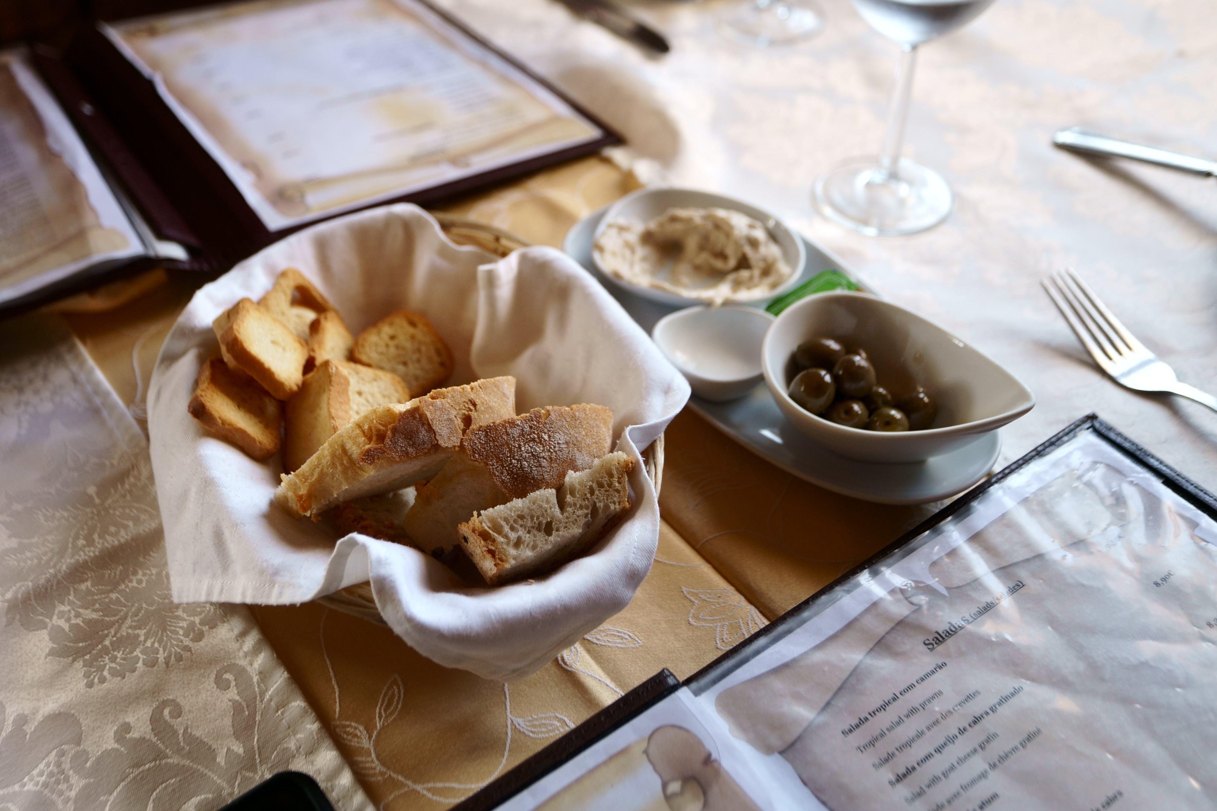 Baked Bread on Basket Besides White Ceramic Bowl