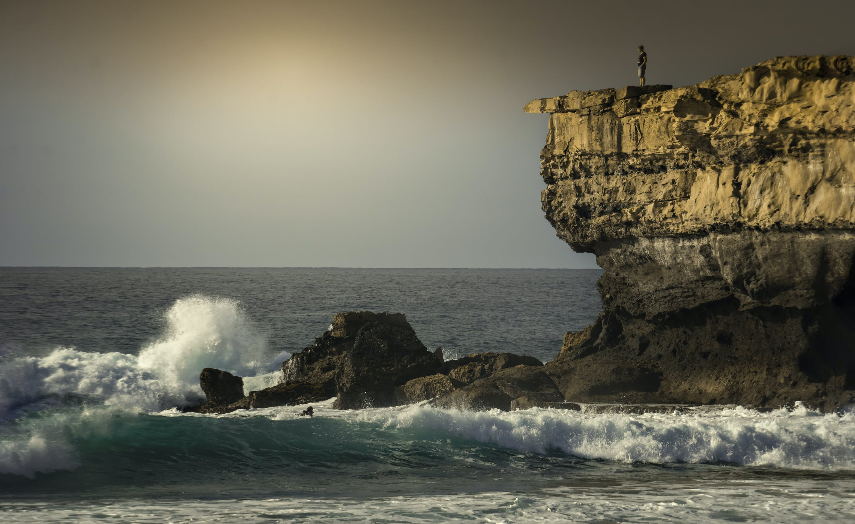 Person Standing on Top of Rock Formation Surrounded by Sea