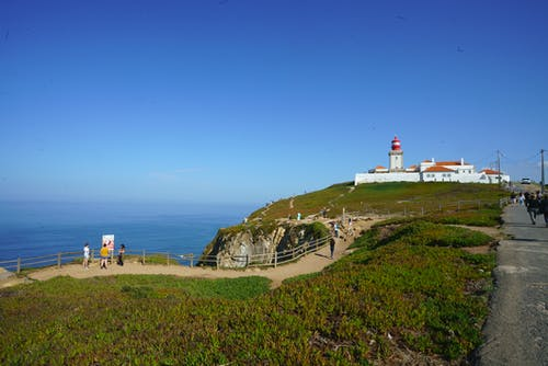 Wide Angle Photo of Lighthouse Under Blue Sky