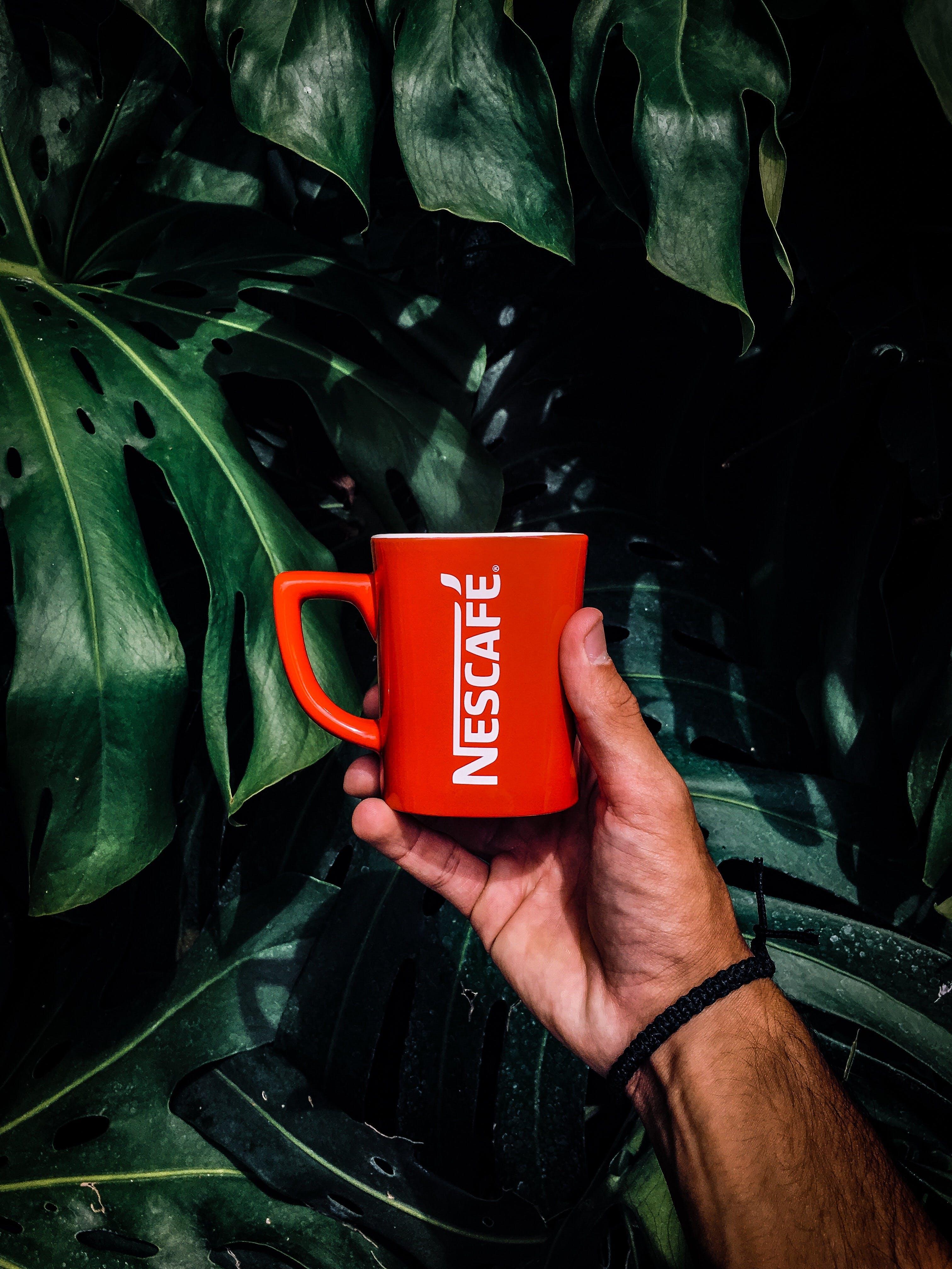 Photo of Man Holding a Red Nescafe Mug