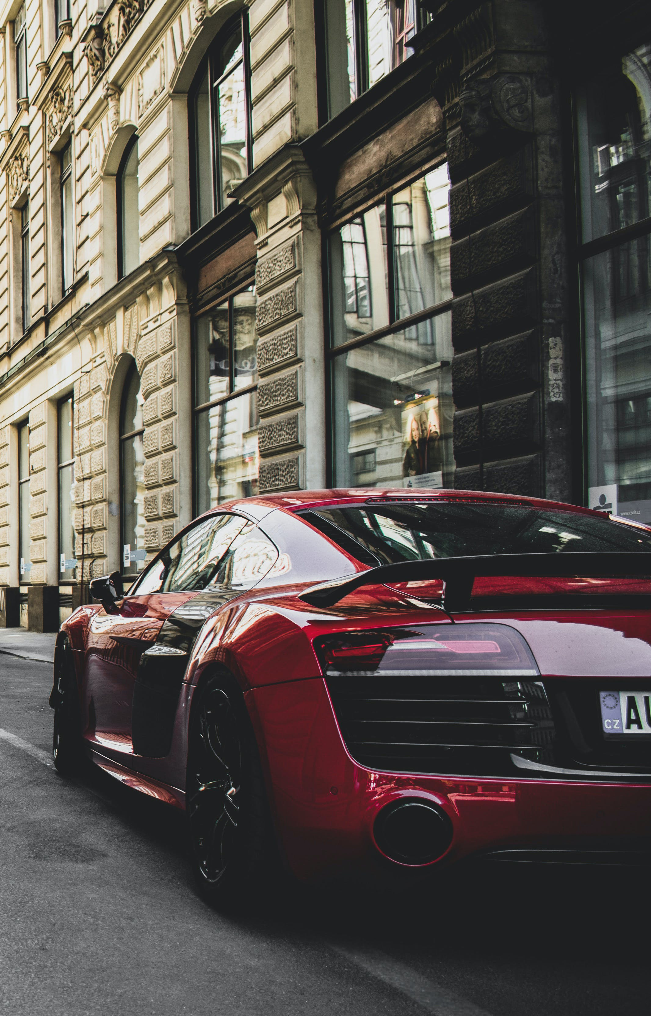 Red and Black Audi R8 Coupe Parked Near Gray Concrete Building