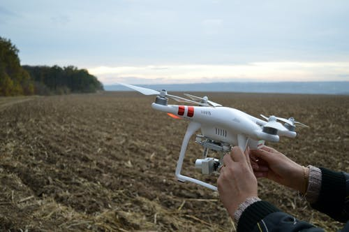 Person Holding Dji Phantom 3 Quadcopter Drone at Open Field
