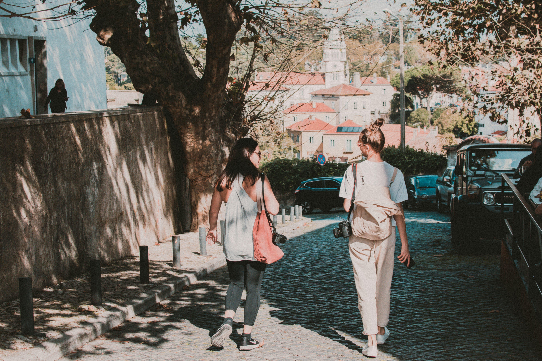 Two Women Walking by Tree