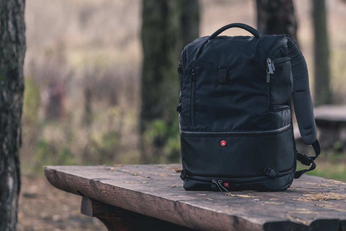 Black Backpack on Top of Wooden Table