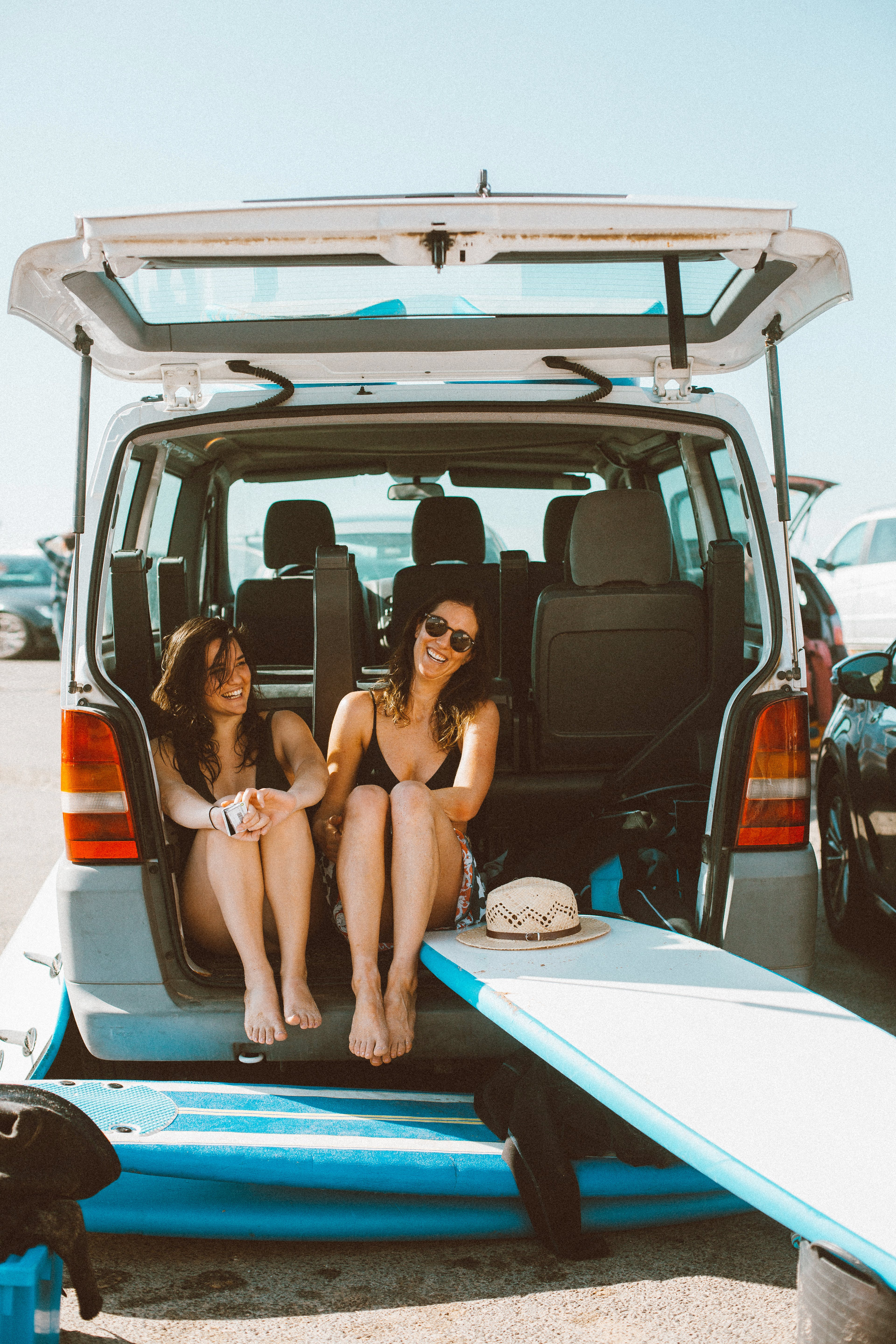 Two Women Sitting on Vehicle's Trunk