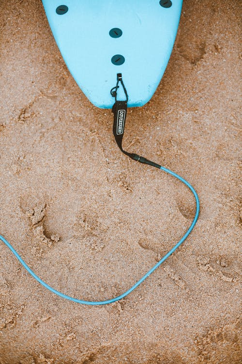 Photo of Blue Surfboard With Leash on Sand