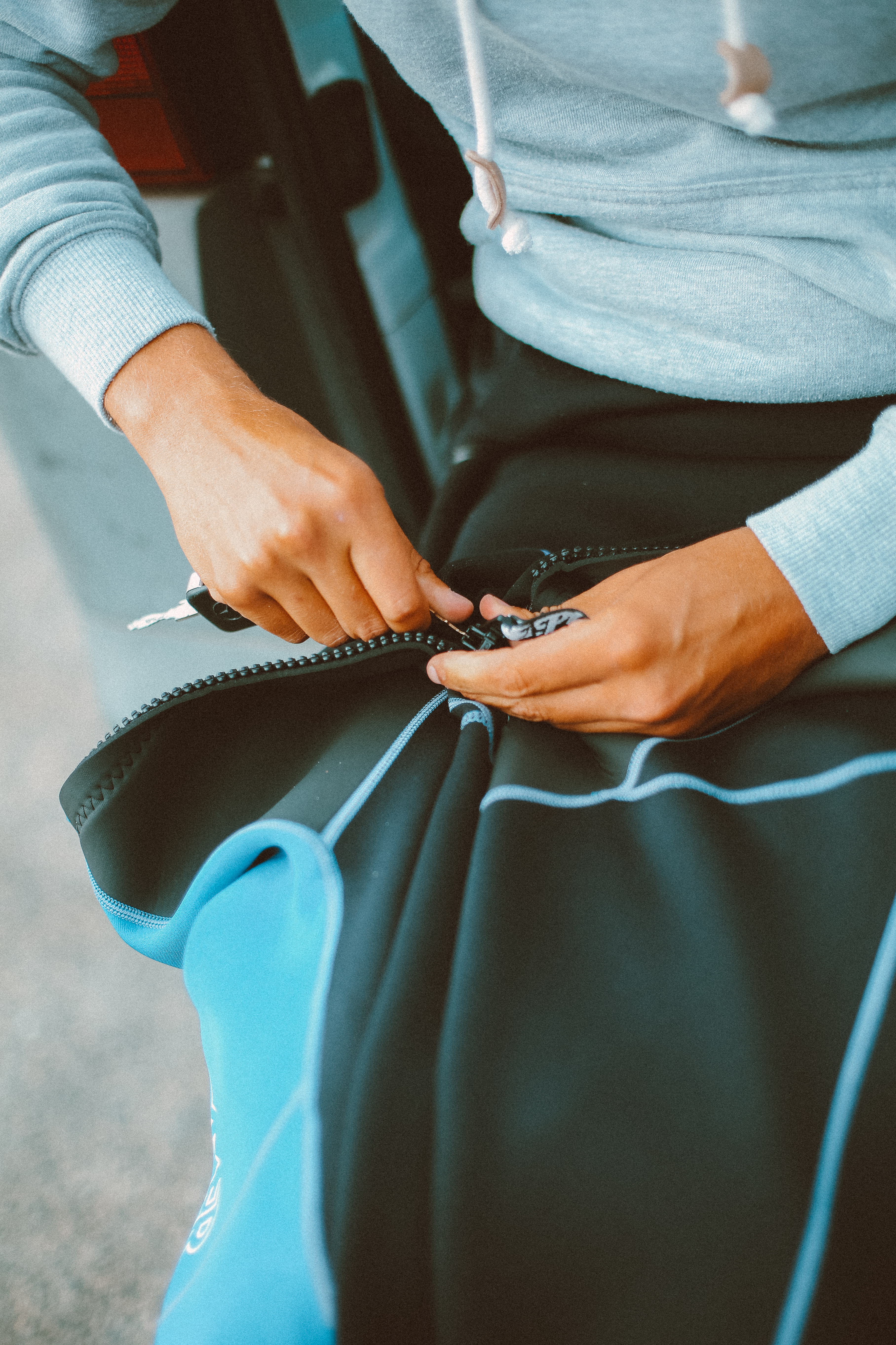 Person Holding the Zipper of Black and Blue Wetsuit
