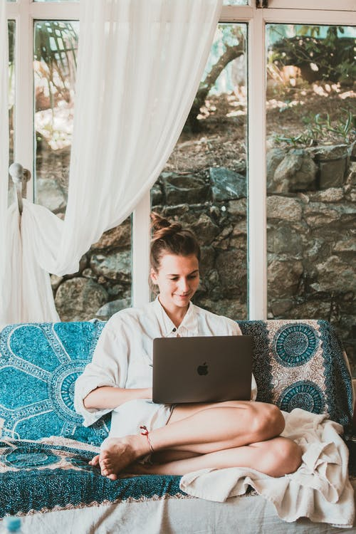 Smiling Woman Using Macbook While Sitting on Sofa