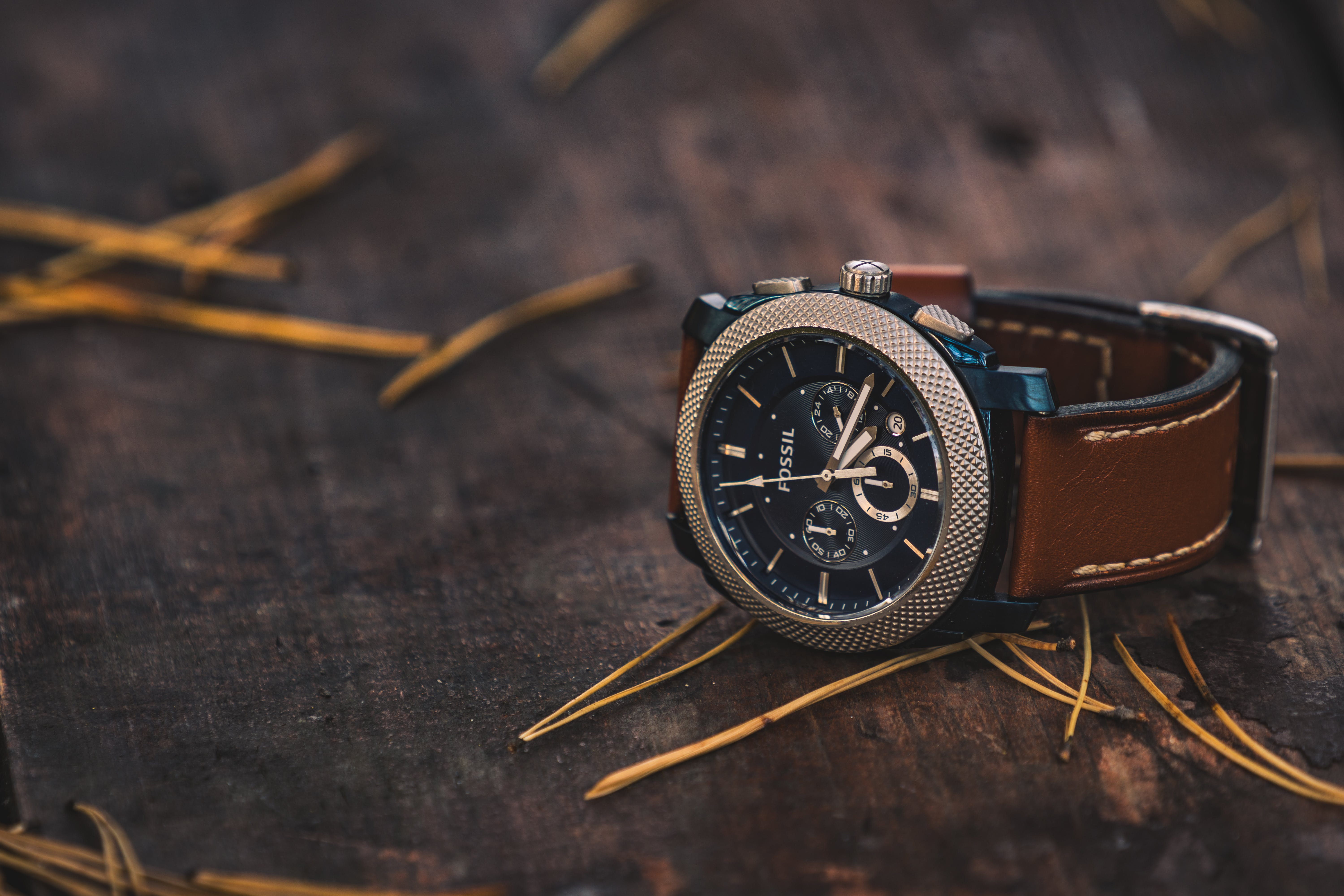 Round Silver Colored Fossil Chronograph Watch With Brown Leather Band On Brown Wooden Surface