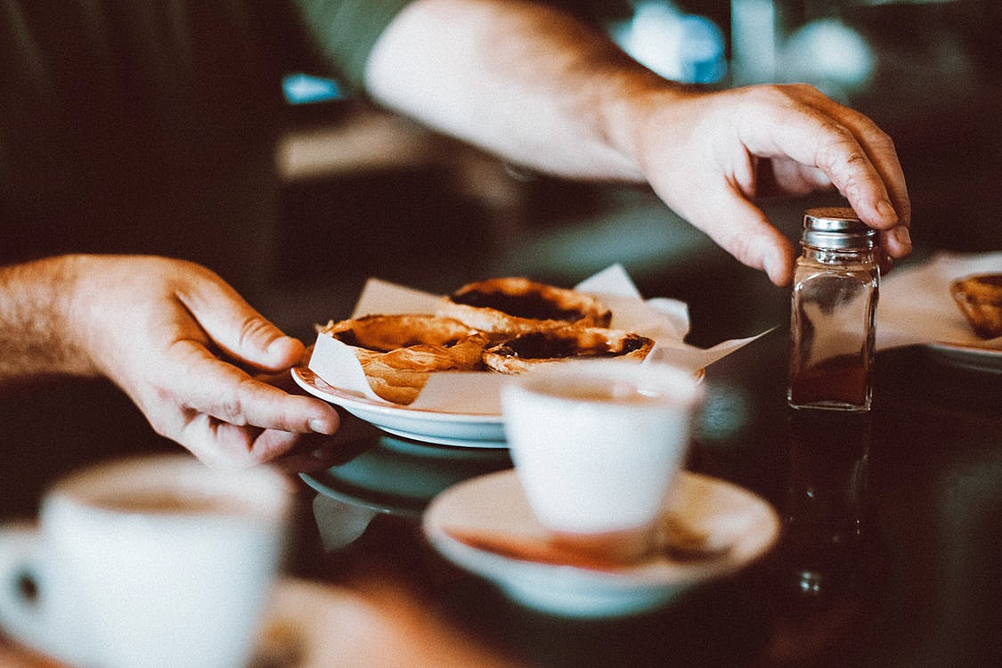 Selective Focus Photography of Man Holding Bowl of Pastry and Condiment Container