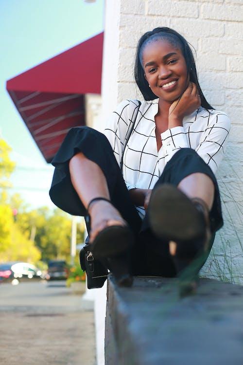 Selektywna Ostrość Fotografii Kobiety Siedzącej Podczas Uśmiechu