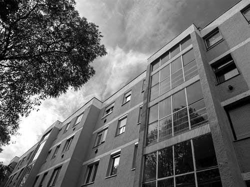 Grayscale Photography of Concrete Building With Glass Window