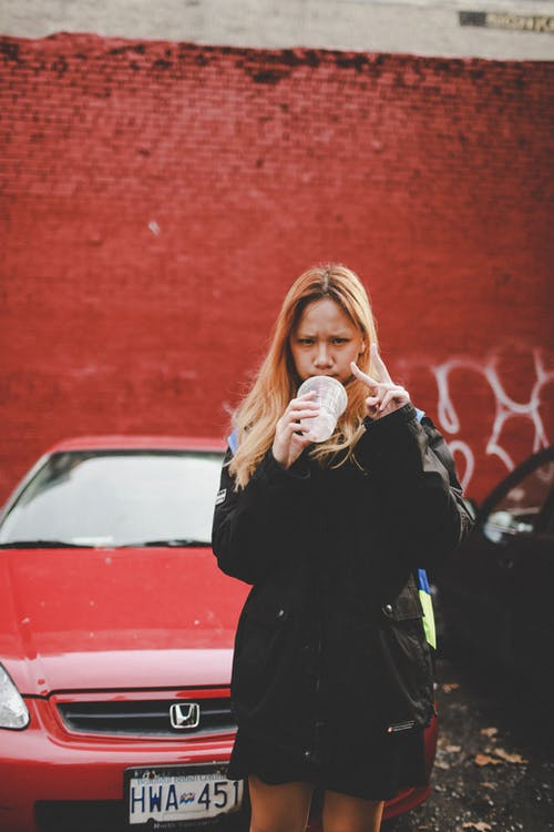 Woman Holding Plastic Cup Beside Red Honda Vehicle