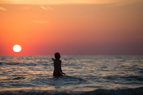 Boy in Ocean during Golden Hour