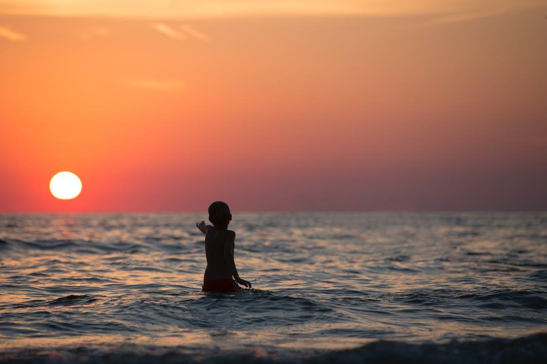 Boy in Ocean during Golden Hour
