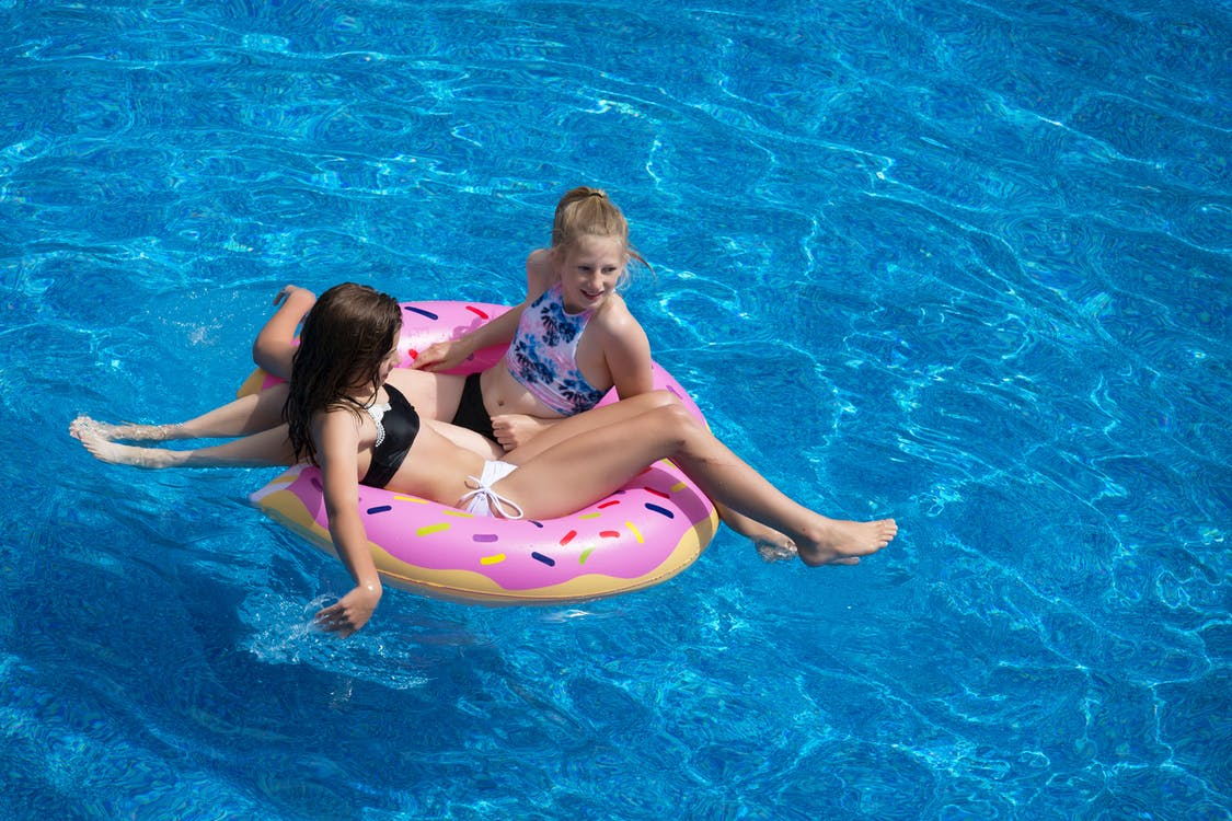 Two Girls Sitting on Pink Doughnut Pool Float