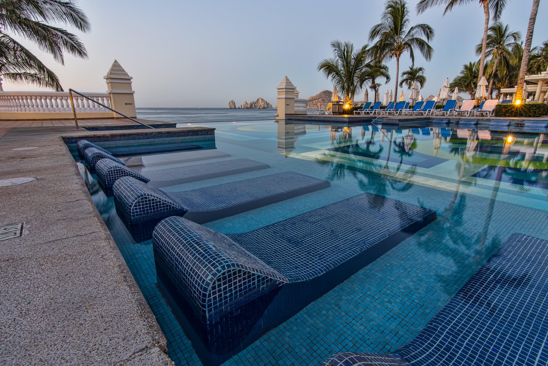Blue Sun Loungers On Swimming Pool